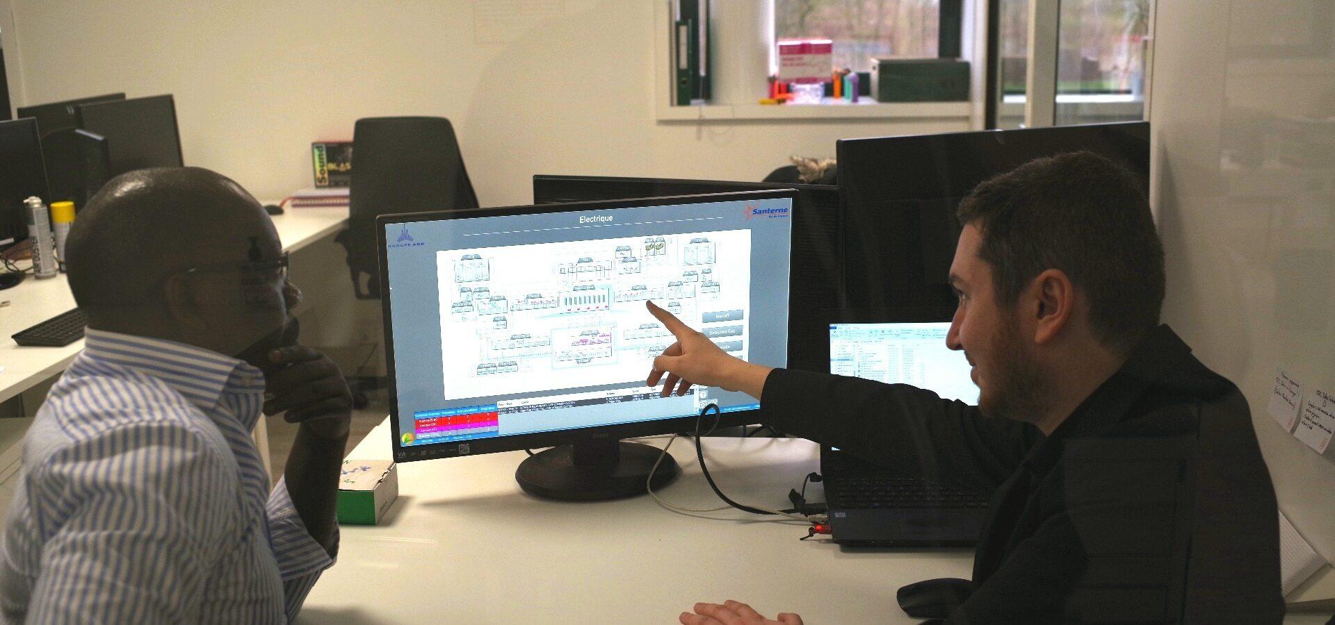 Deux hommes dans un bureau regardent un écran d'ordinateur