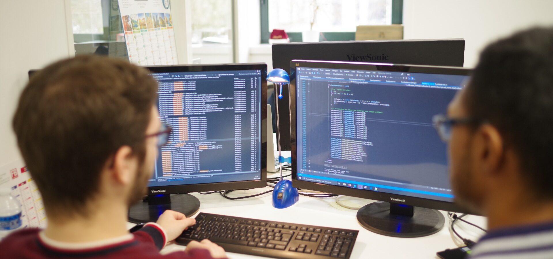 Deux hommes de dos regardent deux écrans avec des lignes de codes