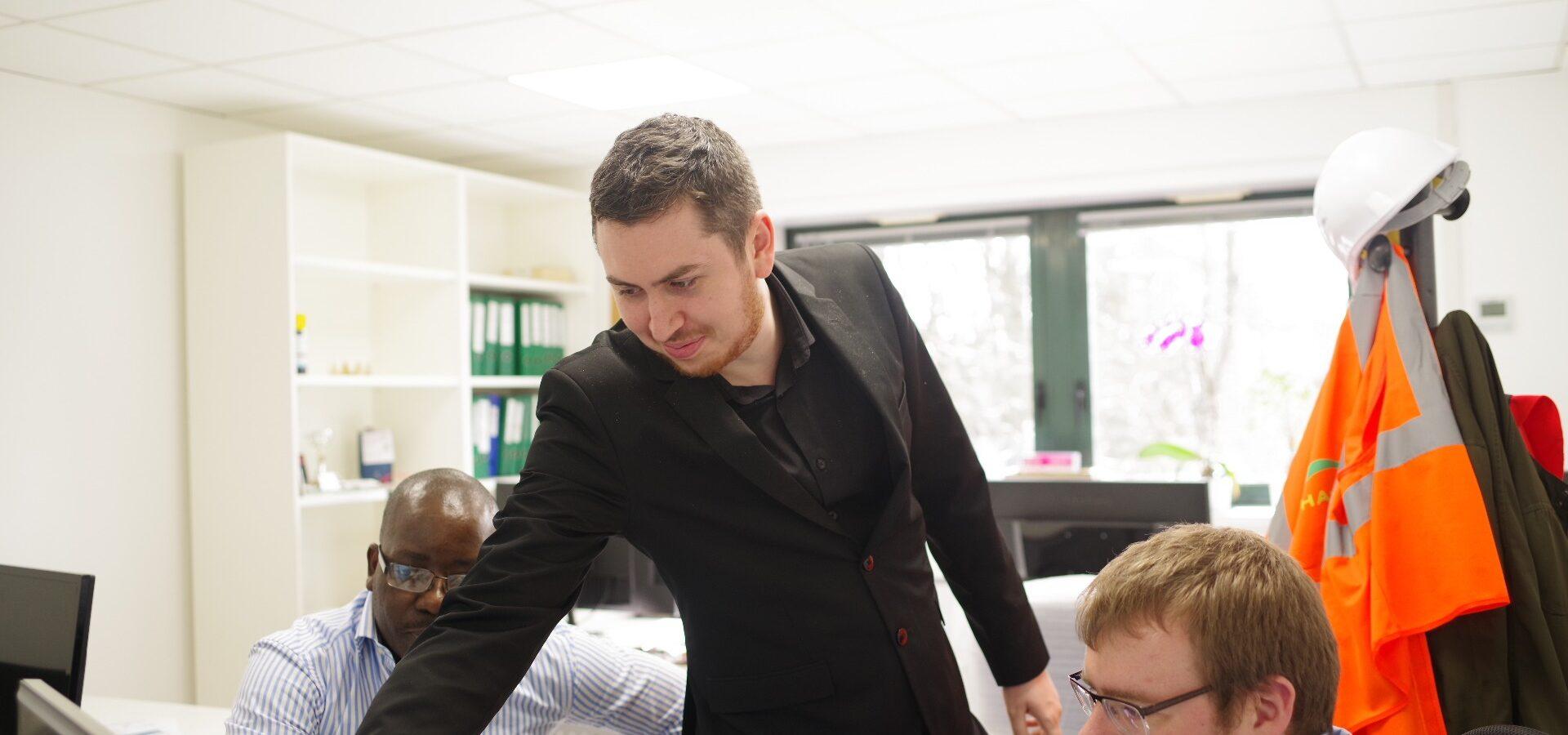 Un homme en costume noir montre un écran à deux autres hommes.